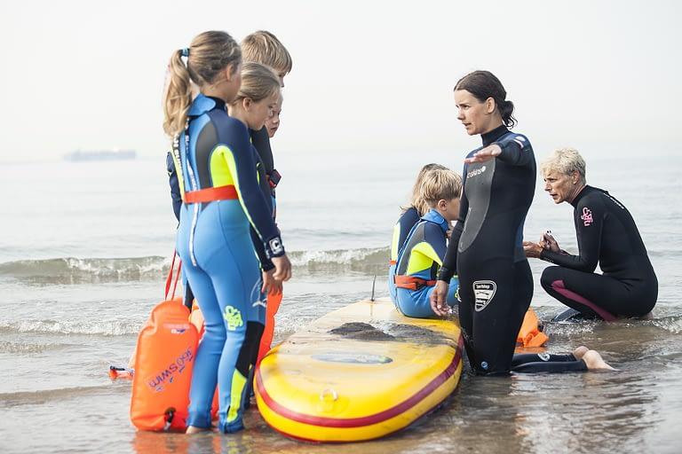 Zwemonderwijzers instrueren leerlingen zwemles aan de Zeeuwse kust