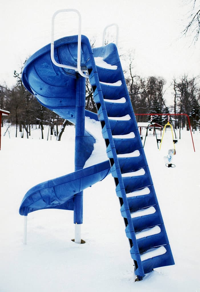 blue playground slide in the snow